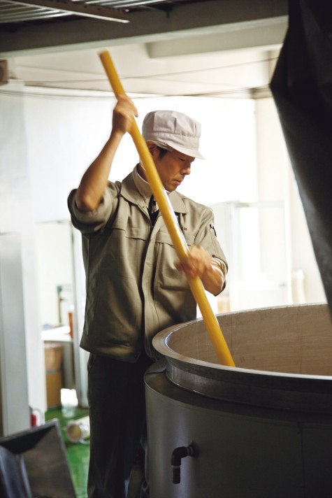 The mash is stirred with a wooden stick.